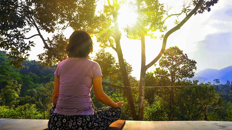 a student meditating on a balcony overlooking nature to relax