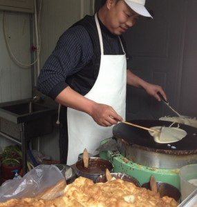 Street vendor cooking Jian Bing Guo Zi