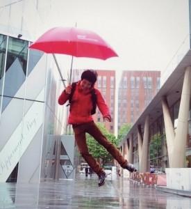 Male student holding umbrella in the rain