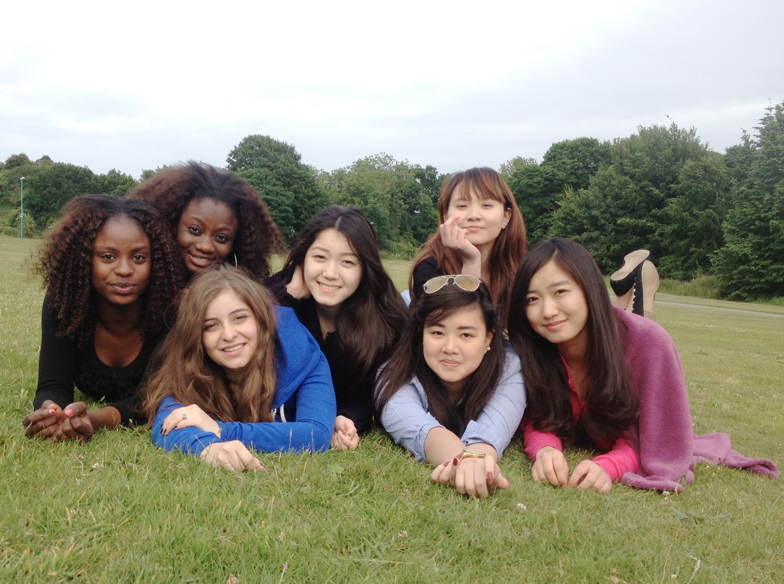 Kristie on grass with friends while studying abroad